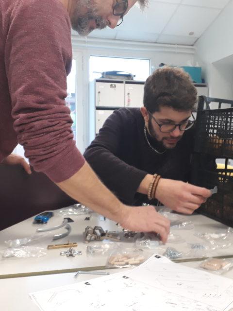 Jérémy et Jérôme concentrés pour le montage d'un meuble pour ranger les jeux de La Courbe
